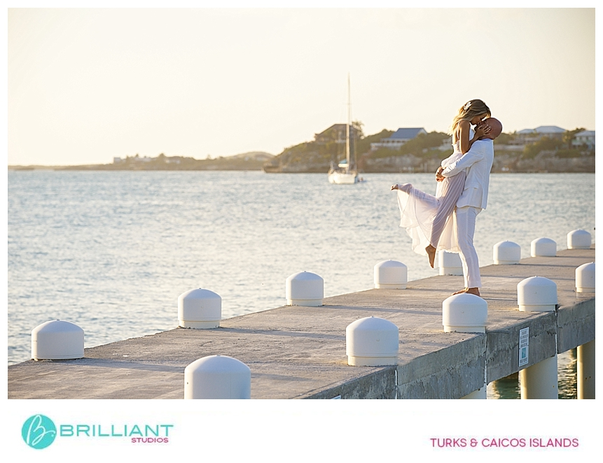 bride an groom kissing on the dock at sapodilla bay